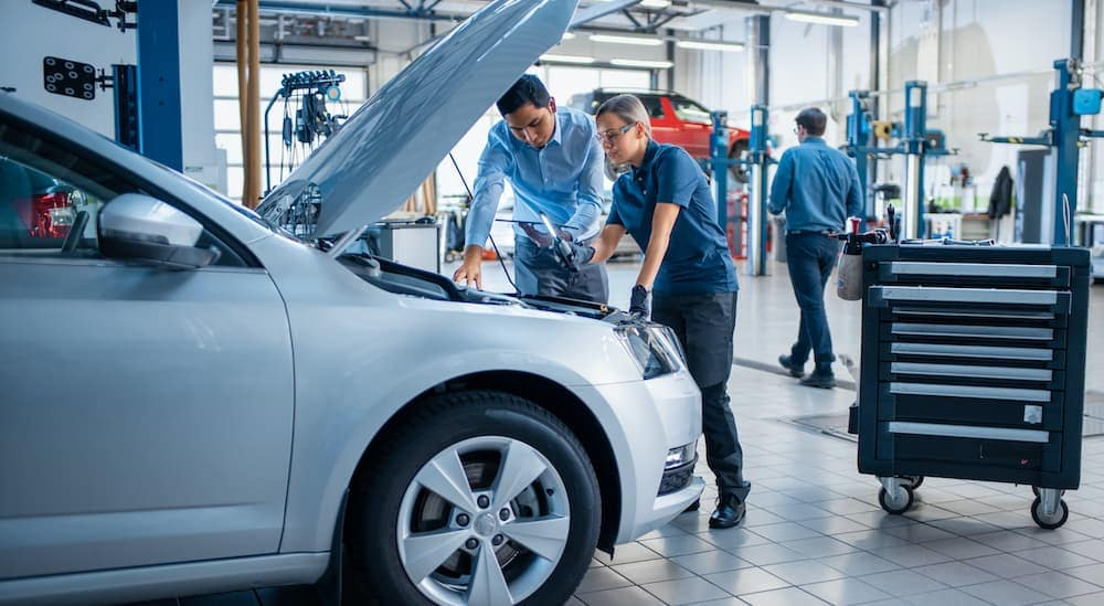 A mechanic and sales person are looking under the hood of a car at a Toyota service department.