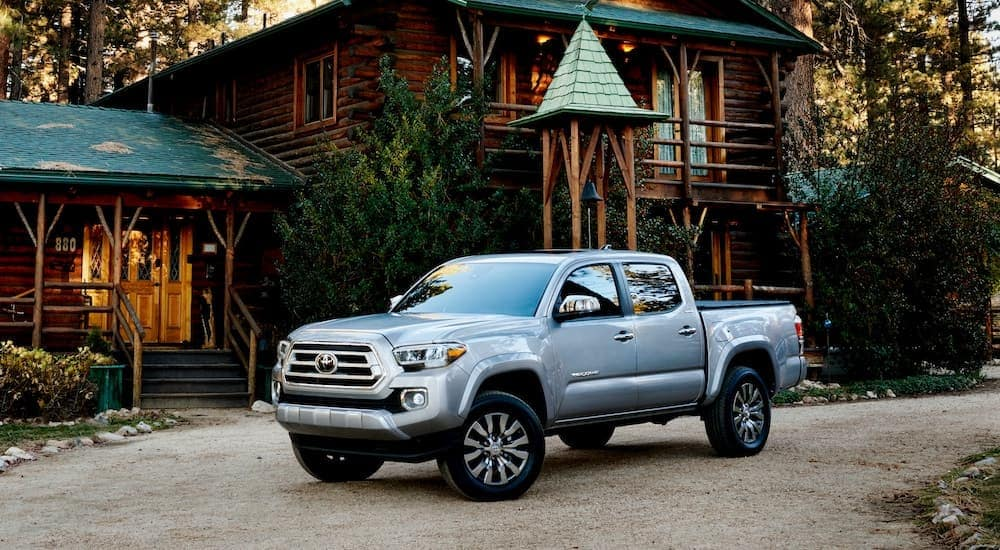 A silver 2021 Toyota Tacoma is parked in front of a log cabin with a green roof.