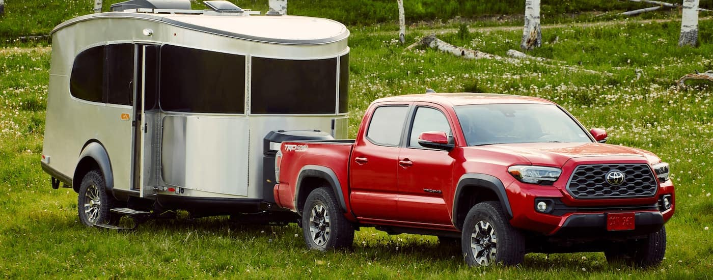 A red 2021 Toyota Tacoma from a Toyota truck dealer is parked on grass with a silver camper.