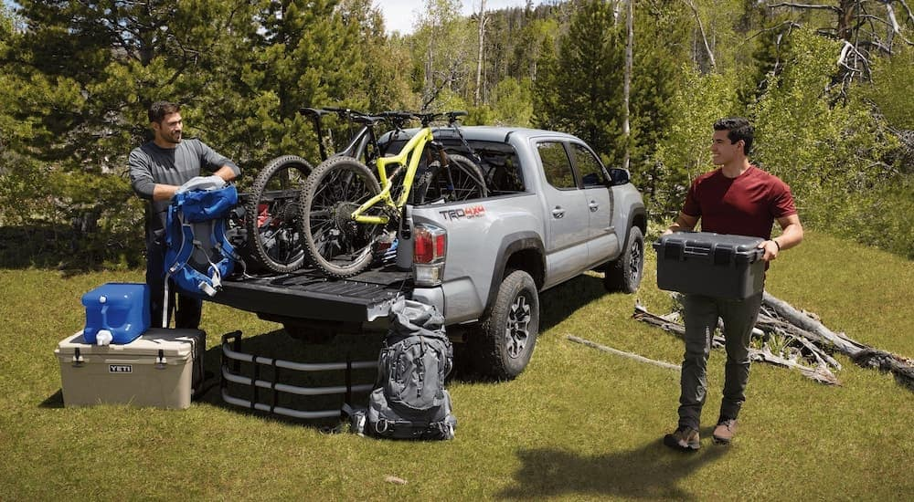 A silver 2021 Toyota Tacoma TRD is shown from behind with bikes in the bed after leaving a Toyota truck dealer.