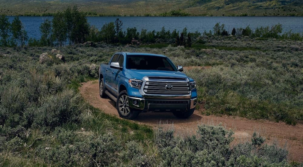 A 2021 blue Toyota Tundra is parked on a dirt path in front of a lake.
