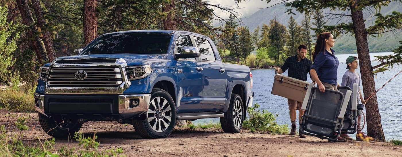 A family has fishing gear at a lake next to a blue 2021 Toyota Tundra.