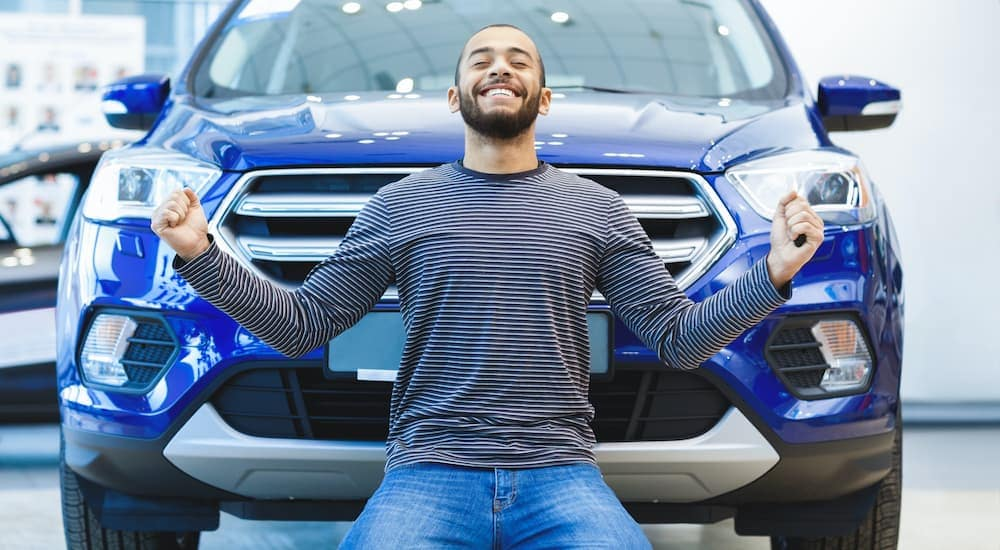 An excited man is on his knees with his hands in the air in front of a blue SUV.