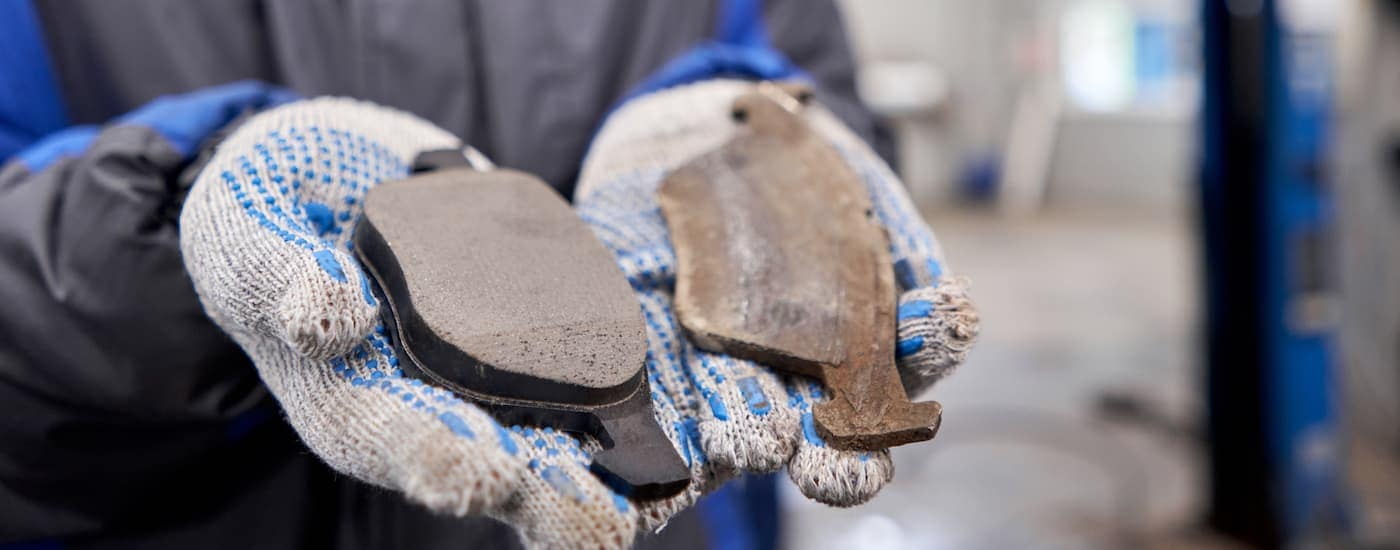 A close up is showing a mechanic holding a new and a used brake pad side-by-side.