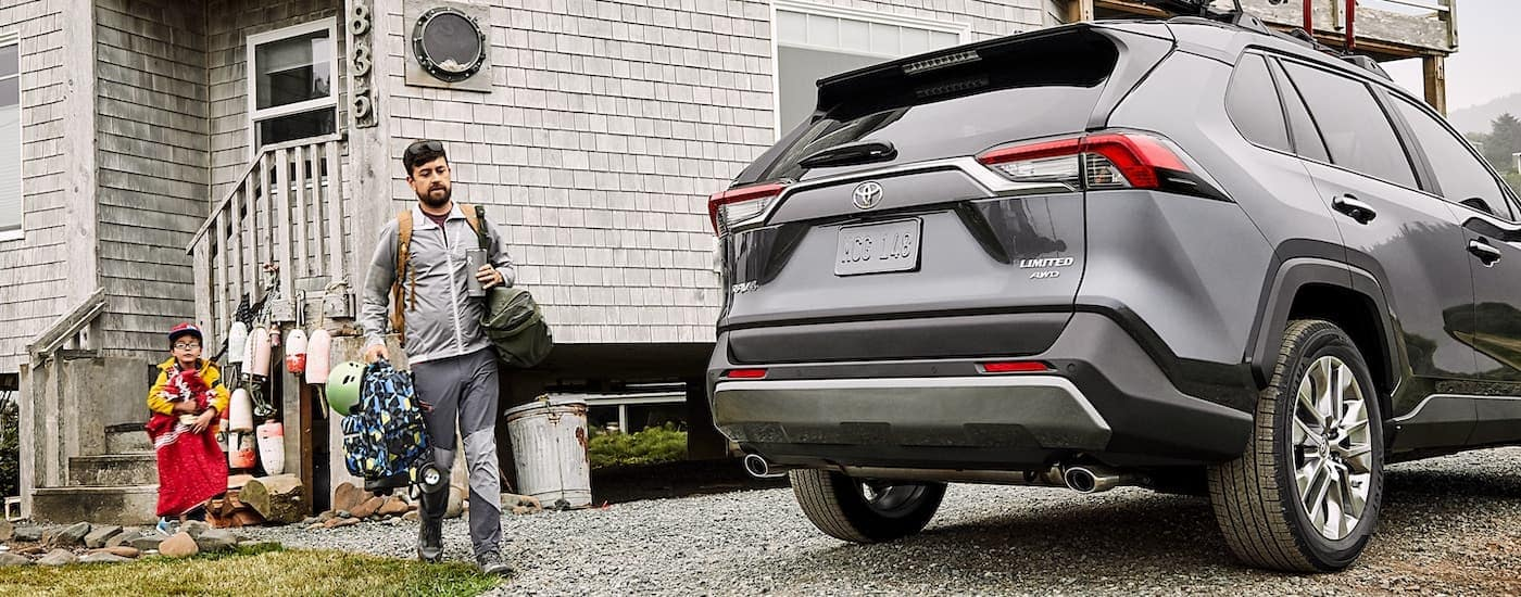 A dark gray 2021 Toyota RAV4 Limited is shown from the rear parked next to a fishing cabin.