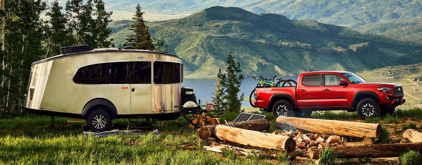 A red 2021 Toyota Tacoma is parked at a campsite with a small, metal camper in front of a lake and mountains.
