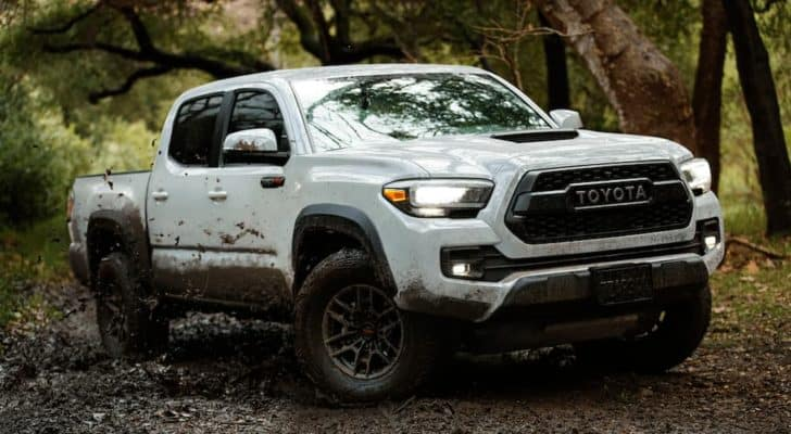 A white 2021 Toyota Tacoma is off-roading in mud after leaving a Toyota Tacoma dealer.