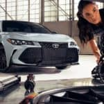 Two mechanics are shown checking the suspension on a white 2021 Toyota Avalon TRD.