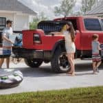 Family packing up a red 2020 RAM 1500 for a beach vacation