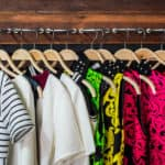 An organized, color-coded closet starting with white shirts, then green, then red.