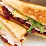 A high angle close up shot of a grilled turkey sandwich with homemade cranberry sauce, mayonnaise, arugula and brie.