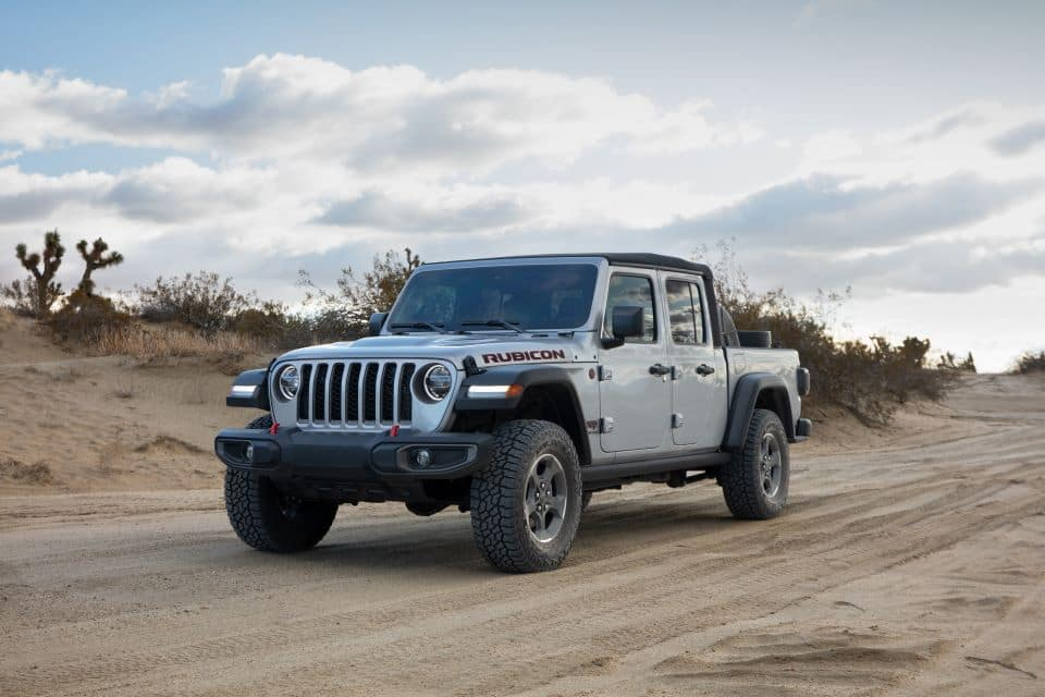 A Silver Jeep Gladiator Rubicon truck driving in the desert.