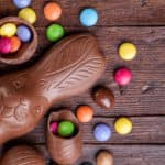 A photo from above of a chocolate bunny and candy eggs on a wooden surface.