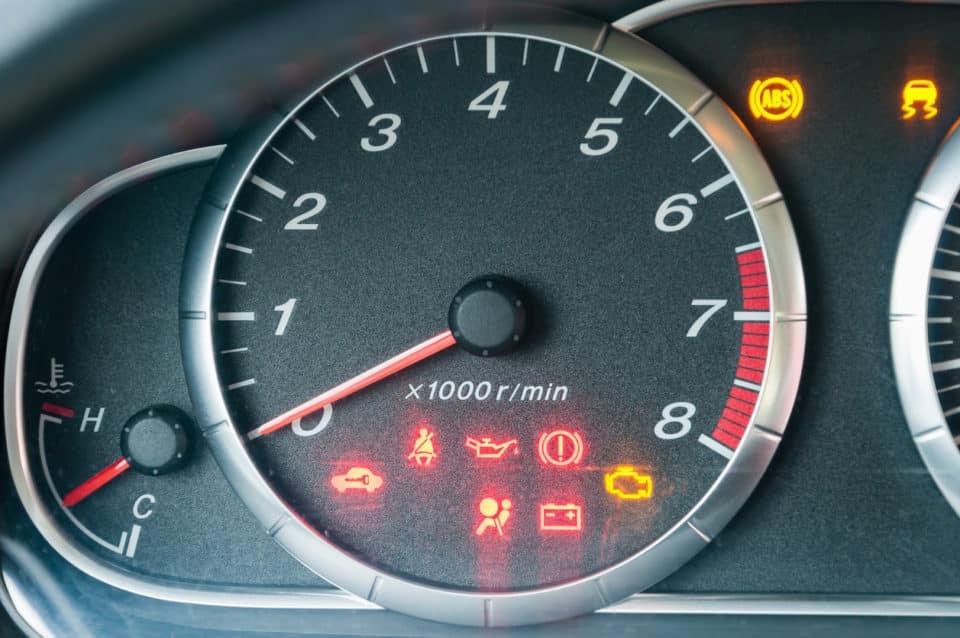 Closeup of car dashboard with many illuminated warning indicators.
