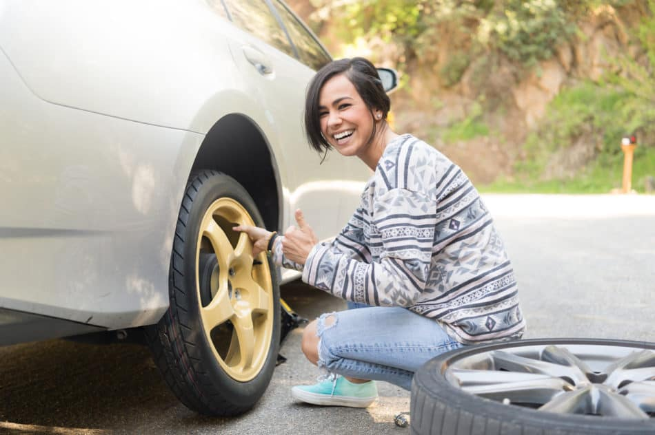 Young woman changing tire on side of the road