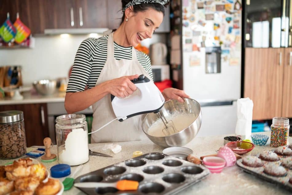 Confectioner woman making delicious cream for cupcakes