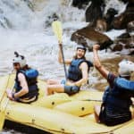 cheerful group of men white water rafting on the river