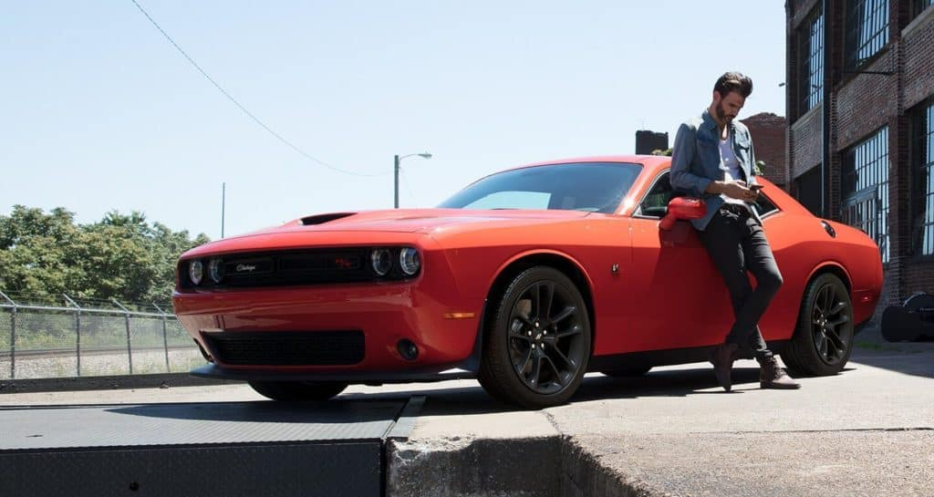 2020 Dodge Challenger Outside Warehouse with Young Handsome Man Leaning on the Car