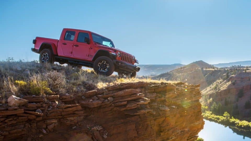 A red 2020 Jeep Gladiator on the edge of a cliff, demonstrating its off-road capabilities