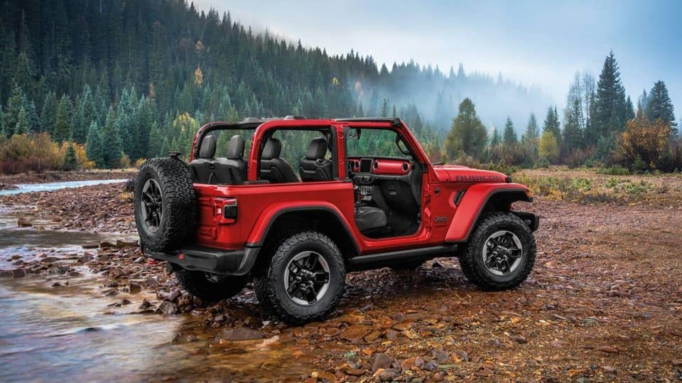 An image of a red two-door 2020 Jeep Wrangler against a mountain on a trail. The doors and top are removed for off-roading.