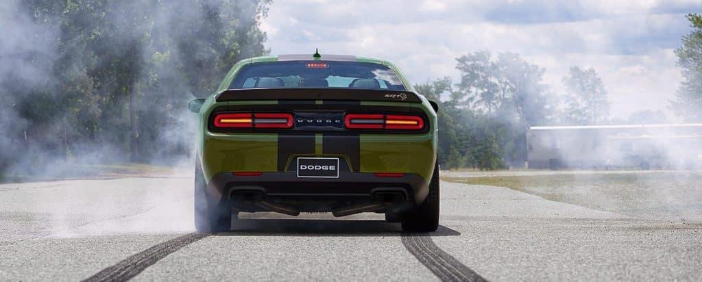 a green dodge challenger burning rubber
