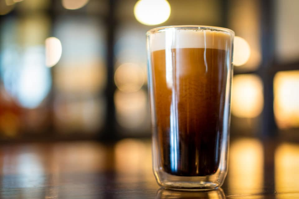 Beautiful texture and layers of Nitro Cold Coffee served in a double wall glass close up.
