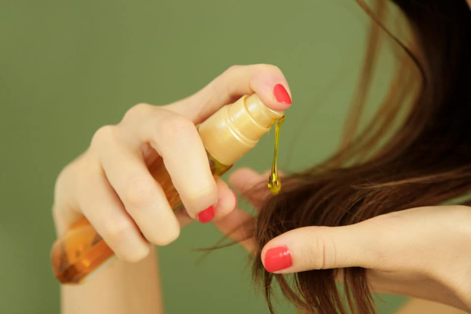 Woman applying hair care product to her hair