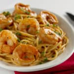 Seared shrimps on a plate of pasta with a parsley garnish in a white bowl.