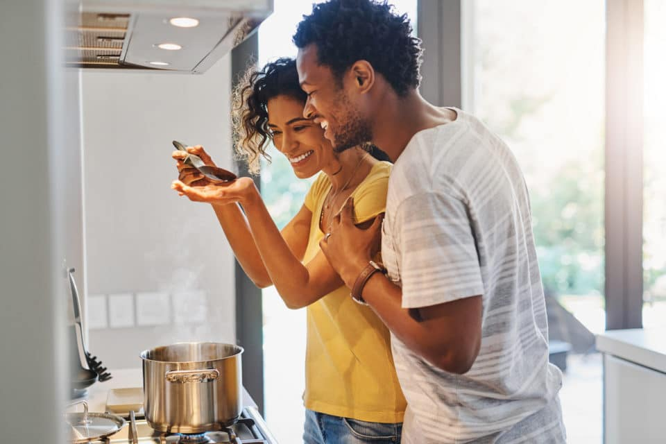 Married couple tasting the food they are making in the kitchen.