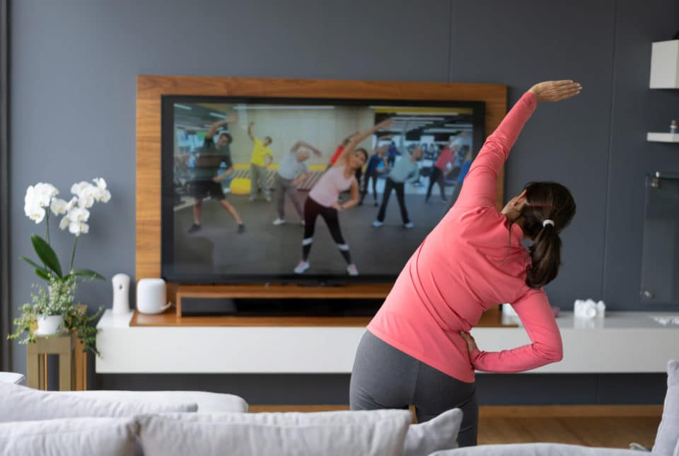 Woman exercising at home with an instruction video
