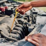 Man checking vehicle oil with dipstick