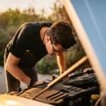 Man checking under the vehicle hood