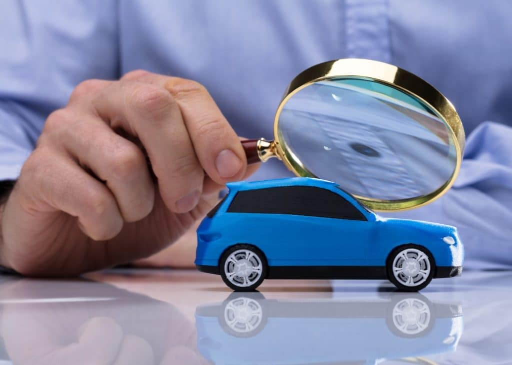miniature car examined with magnifying glass