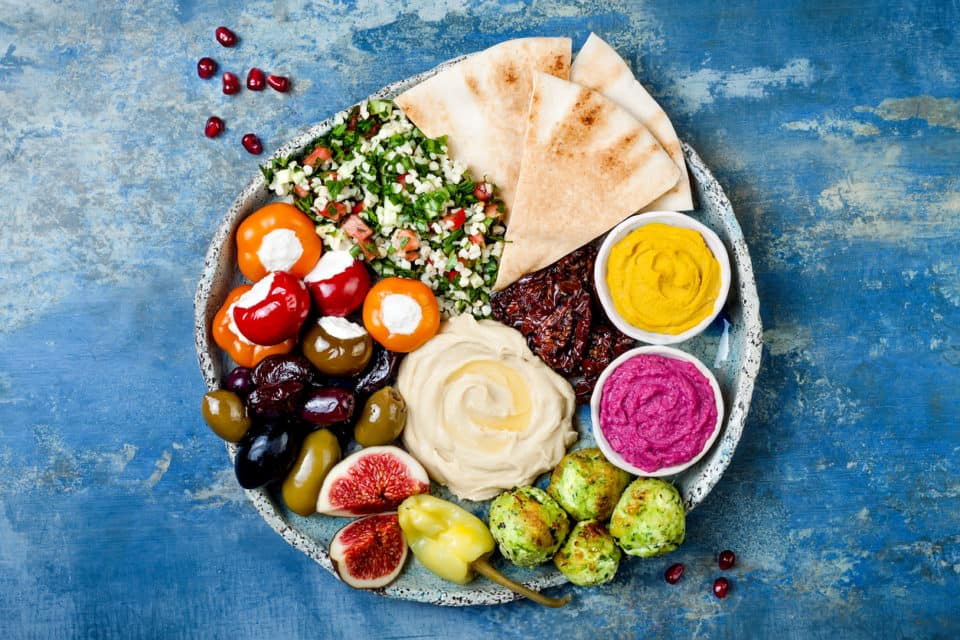 Meze platter with green falafel, pita, sun dried tomatoes, pumpkin and beet hummus, olives, stuffed peppers, tabbouleh, figs. Mediterranean appetizer party idea