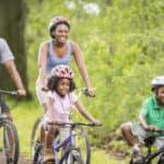 Family riding bikes along a trail