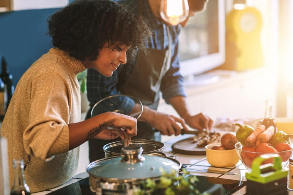 Couple Cooking Together. Standing around the kitchen island, having fun and preparing food together