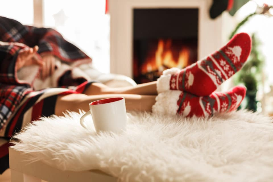Feet in Christmas socks propped up next to a fireplace and a coffee mug