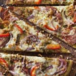Basil Pesto Flat Bread Pizza with Prosciutto, Salami, Pepperoni, Red Peppers and Spanish Onions
