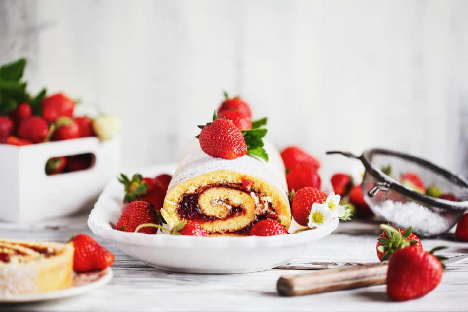 Homemade strawberry shortcake cake roll or Roulade with a berry jam filling and powdered sugar with mint leaves. Dessert over a white rustic wooden table. Selective focus with blurred foreground and background.