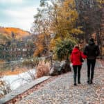 Couple walking by the lake in the forest during the autumn season
