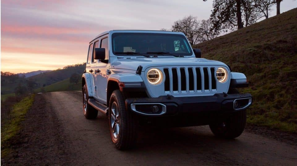 A light blue 2020 Jeep Wrangler against a sunset.