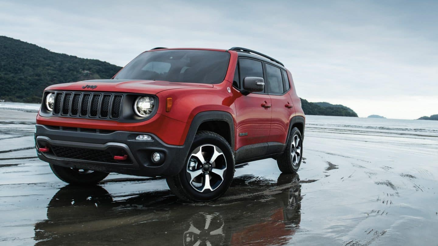 A red 2020 Jeep Renegade driving through a shallow puddle of water.