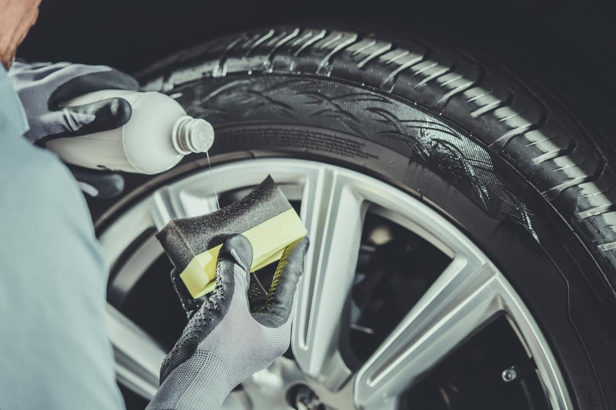 A tire being cleaned with a brush and cleaning solution.