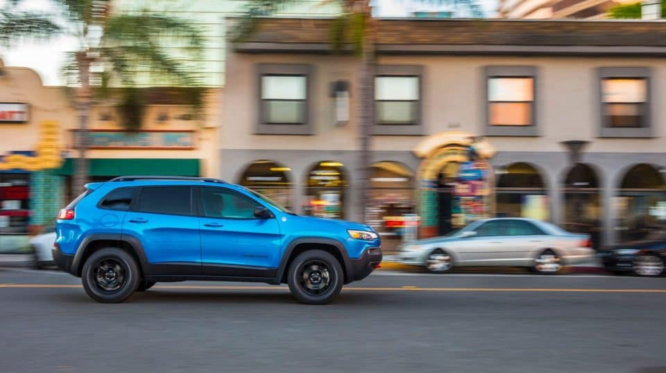 a blue 2020 Jeep Cherokee driving down a city street