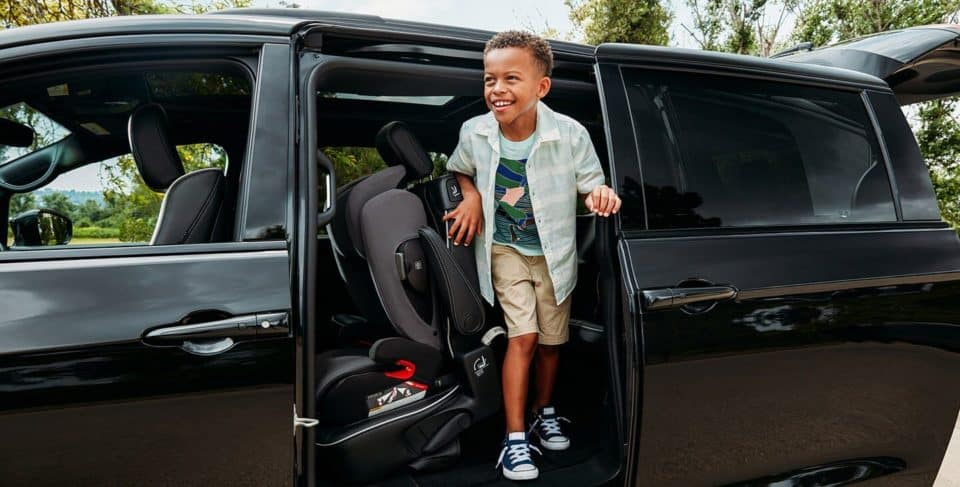 A young boy getting out of a 2020 Chrysler Pacifica, he is smiling.