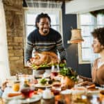 Happy black father bringing Thanksgiving turkey to the table. His wife and two children are sitting at the table that is full with food.