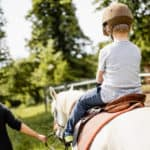 Woman teaching a young boy how to ride a horse