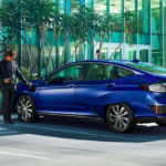 Blue Honda Clarity Electric Plugged in to Charging Station