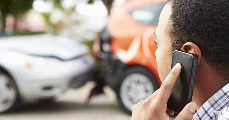 Man on phone with insurance after car crash