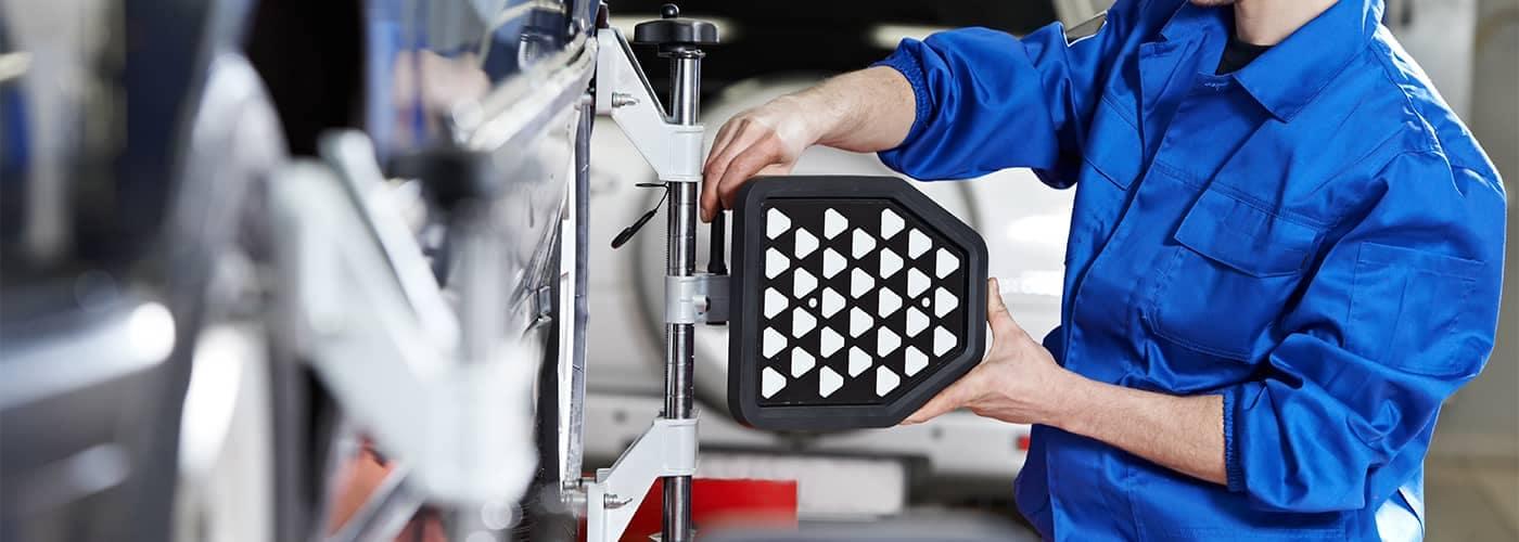 Mechanic aligning wheel